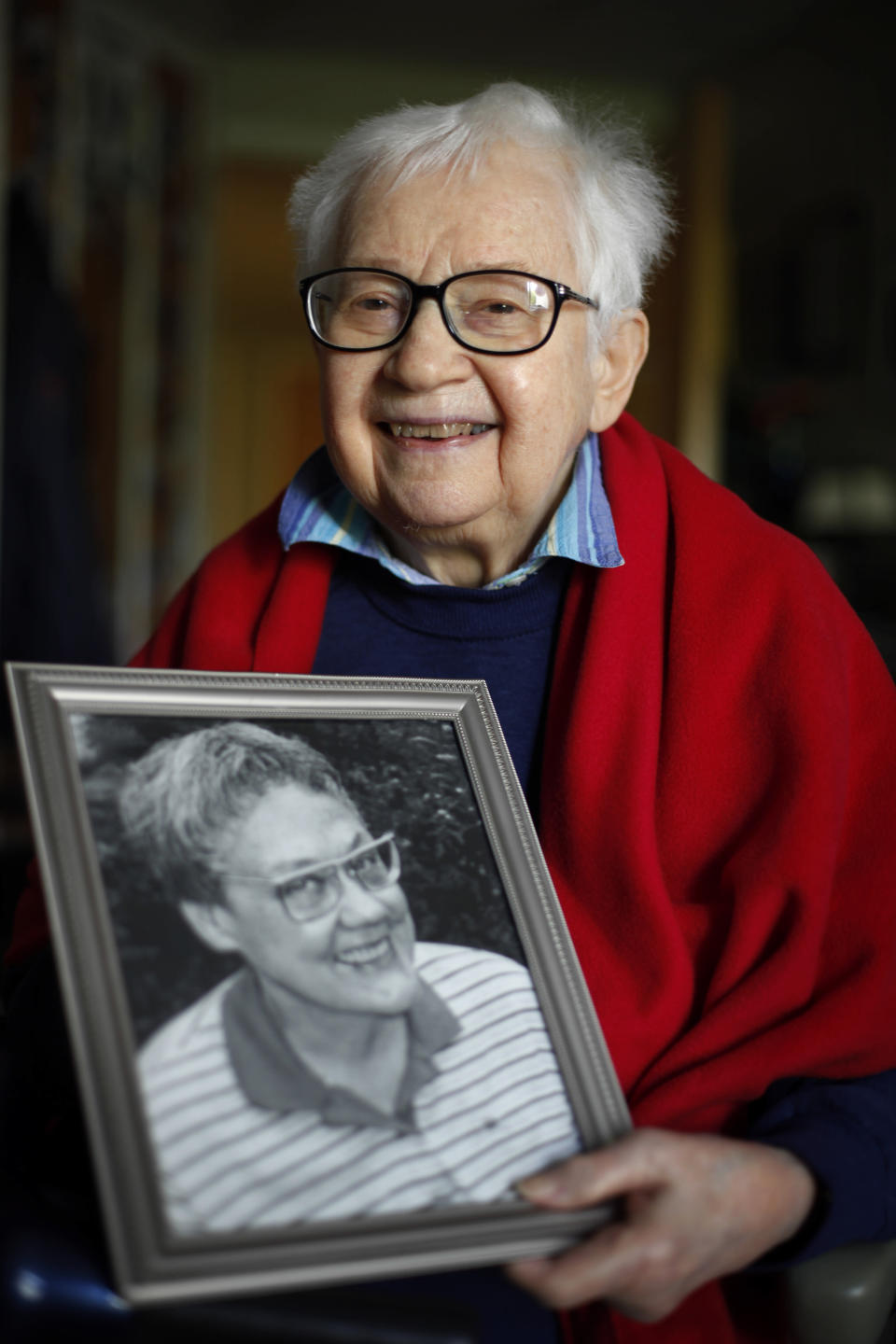 FILE - In this May 10, 2012 file photo, Kay Tobin Lahusen poses for a photograph with a portrait of her late partner Barbara Gittings, in Kennett Square, Pa. Lahusen, a pioneering gay rights activist who chronicled the movement's earliest days through her photography and writing, has died. She was 91. Known as the first openly gay photojournalist, Lahusen died Wednesday, May 26, 2021, at Chester County Hospital outside Philadelphia following a brief illness, according to Founds Funeral Home. (AP Photo/Matt Rourke, File)