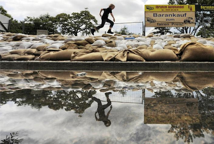 A child runs over a wall of sandbags at river Elbe in Dresden, eastern Germany, Thursday, June 6, 2013. Heavy rainfalls caused flooding along rivers and lakes in Germany, Austria, Switzerland and the Czech Republic. Second-hand car dealer advertisement at right reads, Buying for cash with fair prices. (AP Photo/Jens Meyer)