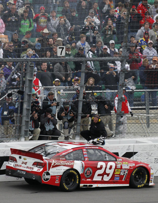 Driver Kevin Harvick (29) picks up the checkered flag after winning the NASCAR Sprint Cup series auto race at Kansas Speedway in Kansas City, Kan., Sunday, Oct. 6, 2013. (AP Photo/Colin E. Braley)