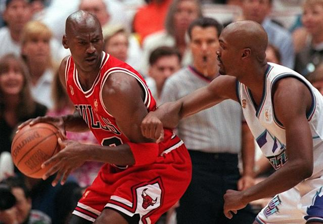 Michael Jordan scowls over his shoulder as he is guarded closely by Utah's Bryon Russell during the 1998 NBA Finals. (AP Photo/Douglas C. Pizac)