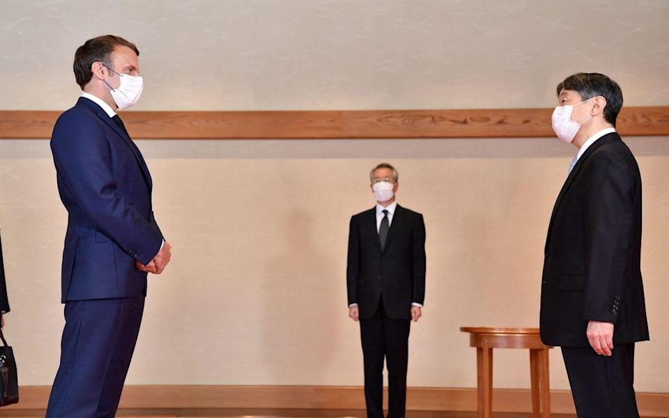 France's President Emmanuel Macron (L) meeting with Japan's Emperor Naruhito (R) - AFP via Getty Images
