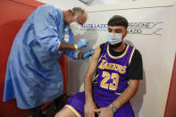 A student is administered his first dose of Pfizer/BioNTech Covid-19 vaccine, at a vaccination hub in a shopping mall in the outskirts of Rome, Tuesday, June 1, 2021. Eighteen-year-old students in Rome were administered their first dose of the Pfizer/BioNTech vaccine in Rome on Tuesday, in view of their upcoming final exams. The vaccination hub at the Porta di Roma Mall on the outskirts of Rome began vaccinating students ahead of their finals which begin in a few weeks. (AP Photo/Andrew Medichini)