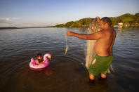 A fisherman plays with his daughter as he works in Alter do Chao, district of Santarem, Para state, Brazil, Wednesday, Aug. 26, 2020. This once pristine place is discovering that the perils of becoming a can't-miss destination extend beyond hordes of weekend warriors sapping the unspoiled place of its charm. (AP Photo/Andre Penner)
