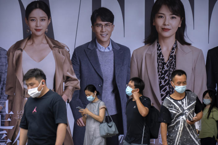 People wearing face masks to help protect against COVID-19 walk past an advertising billboard at a subway station during the morning rush hour in Beijing, Wednesday, Aug. 4, 2021. China's worst coronavirus outbreak since the start of the pandemic a year and a half ago escalated Wednesday with dozens more cases around the country, the sealing-off of one city and the punishment of its local leaders. (AP Photo/Mark Schiefelbein)