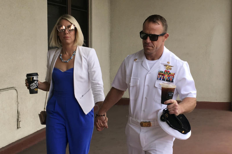 Navy Special Operations Chief Edward Gallagher, right, walks with his wife, Andrea Gallagher as they arrive to military court on Naval Base San Diego, Wednesday, June 26, 2019, in San Diego. Trial continues in the court-martial of the decorated Navy SEAL, who is accused of stabbing to death a wounded teenage Islamic State prisoner and wounding two civilians in Iraq in 2017. He has pleaded not guilty to murder and attempted murder, charges that carry a potential life sentence. (AP Photo/Julie Watson)
