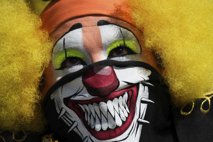 A clown in a face mask protests restrictions to contain the spread of COVID-19 which bar clowns from working on the streets outside the National Palace in Mexico City, Thursday, April 30, 2020. (AP Photo/Fernando Llano)