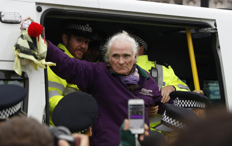 Police officers arrest a climate protestor in Trafalgar Square in central London Monday, Oct. 7, 2019. Extinction Rebellion movement blocked major roads in London, Berlin and Amsterdam on Monday at the beginning of what was billed as a wide-ranging series of protests demanding new climate policies. (AP Photo/Alastair Grant)