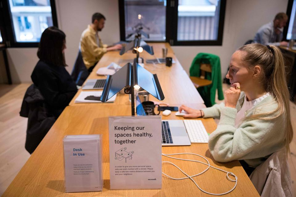 People work at shared workspaces at the WeWork, coworking and office space in the City of London. Photo: Tolga Akmen/AFP via Getty Images