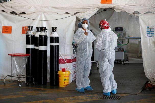 FILE PHOTO: Health care workers chat at a temporary ward setup, during the COVID-19 outbreak, at Steve Biko Academic Hospital in Pretoria, South Africa, Jan. 19, 2021. (Phill Magakoe/Pool via REUTERS)