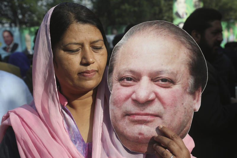 A supporter of Pakistan's ailing former Prime Minister Nawaz Sharif, holds a picture of him at an airport in Lahore, Pakistan, Tuesday, Nov. 19, 2019. Sharif has arrived at the airport to board a plane after a court granted him permission to leave for four weeks abroad for medical treatment. (AP Photo/K.M. Chaudary)