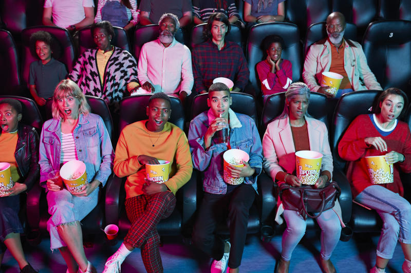 Shocked audience enjoying thriller movie with popcorn at cinema hall