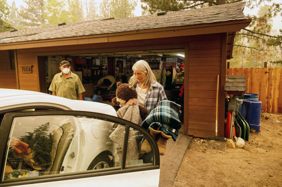 As the Caldor Fire approaches, Patty Kingsbury carries blankets and a teddy bear while evacuating from her South Lake Tahoe, Calif. home on Friday, Aug. 27, 2021. (AP Photo/Noah Berger)