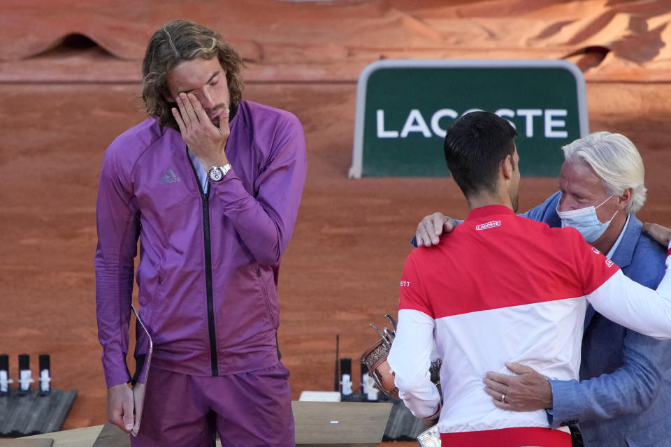 Former Swedish tennis ace Bjorn Borg, right, gives the cup to Serbia's Novak Djokovic while Stefanos Tsitsipas of Greece, left, react after their final match of the French Open tennis tournament at the Roland Garros stadium Sunday, June 13, 2021 in Paris. (AP Photo/Christophe Ena)