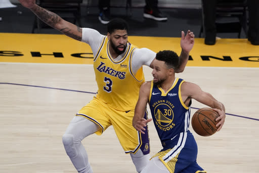 Los Angeles Lakers' Anthony Davis, left, pressures Golden State Warriors' Stephen Curry during the second half of an NBA basketball game, Monday, Jan. 18, 2021, in Los Angeles. The Warriors won 115-113. (AP Photo/Jae C. Hong)