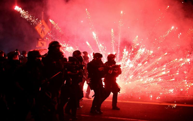 Police advance on protesters to clear a street on the 100th consecutive night of protests against police violence and racial inequality, in Portland, Oregon - Reuters