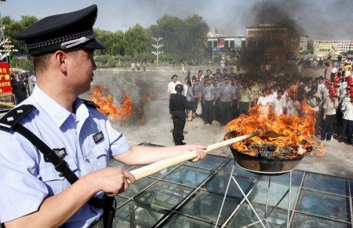 A Chinese policeman lits a cauldron filled with illicit drugs during a 2009 ceremony in Hami, Xinjiang region