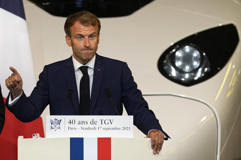 """French President Emmanuel Macron speaks in front of a life-size replica of the next high-speed train TGV, at the Gare de Lyon station Friday, Sept. 17, 2021 in Paris. France unveils a super-fast, climate-friendly train of the future, the next generation of its high-speed TGV trains that have been emulated around the world. French President Emmanuel Macron and other government officials are holding a ceremony at the historic Gare de Lyon train station in Paris to mark 40 years since the unveiling of the first TGV, or """"train a grand vitesse."""" (AP Photo/Michel Euler, Pool)"""