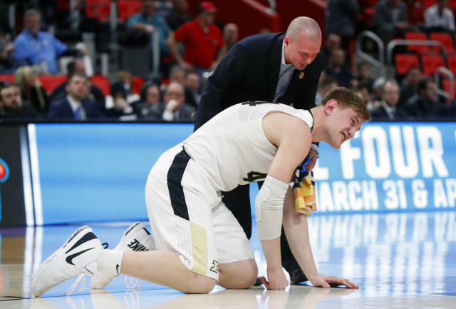 Purdue center Isaac Haas reacts to landing on the floor as a trainer attends to him against Cal State Fullerton during the second half of an NCAA men's college basketball tournament first-round game in Detroit, Friday, March 16, 2018. (AP Photo/Paul Sancya)