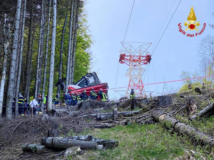 Rescuers work by the wreckage of a cable car after it collapsed near the summit of the Stresa-Mottarone line in the Piedmont region, northern Italy, Sunday, May 23, 2021. A cable car taking visitors to a mountaintop view of some of northern Italy's most picturesque lakes plunged to the ground Sunday, killing at least nine people and sending two children to the hospital, authorities said. (Italian Vigili del Fuoco Firefighters via AP)