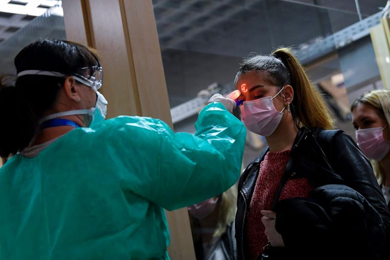 Airport staff check the temperatures of passengers returning from Milan as part of the coronavirus screening procedure at the Debrecen airport, Hungary, Tuesday, Feb. 25, 2020.