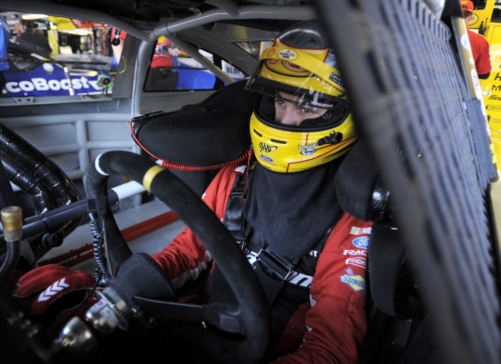 Joey Logano waits in his car before a NASCAR Sprint Cup series auto race practice at Darlington Speedway in Darlington, S.C., Friday, April 11, 2014. (AP Photo/Mike McCarn)