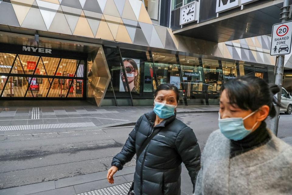 Pedestrians wearing face masks walk past a closed major department store in the Melbourne's Central Business District.