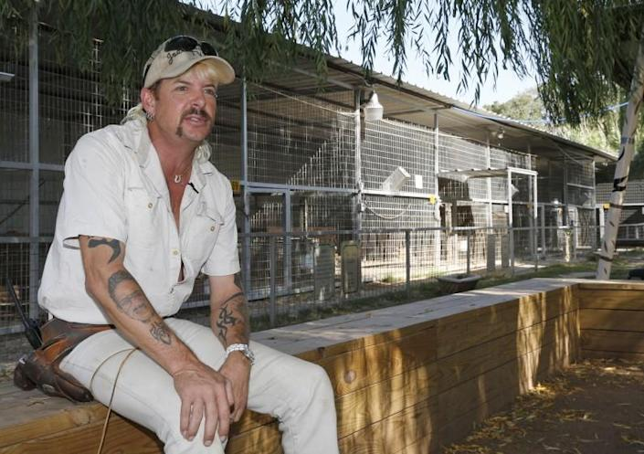 A man with a mustache and a ball cap sits near animal cages
