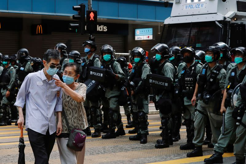A couple walks past riot police as anti-national security law protesters march during the anniversary of Hong Kong's handover to China from Britain, in Hong Kong