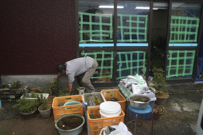A man puts off things at a flower shop as Typhoon Hagibis approaches in town of Kiho, Mie Prefecture, Japan Friday, Oct. 11, 2019. A powerful typhoon was forecast to bring 2 feet of rain and damaging winds to the Tokyo area this weekend, and Japan's government warned people Friday to stockpile supplies and evacuate before it's too dangerous. (AP Photo/Toru Hanai)