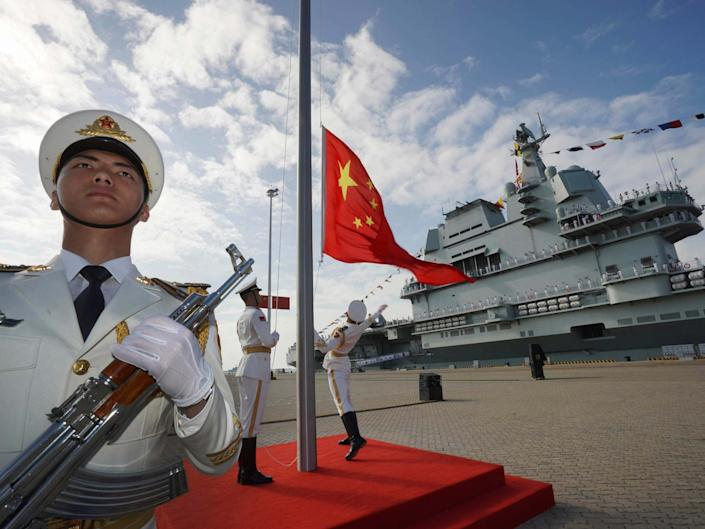 Chinese honor guard raise the Chinese flag during the commissioning ceremony of China's Shandong aircraft carrier: AP
