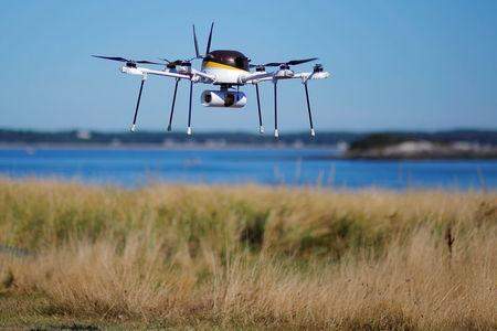 A drone, made by CyPhy Works, carries a UPS package on Children's Island off the coast of Beverly, Massachusetts during UPS's demonstration of a drone making a commercial delivery of a package to a remote or difficult-to-access location. REUTERS/Brian Snyder