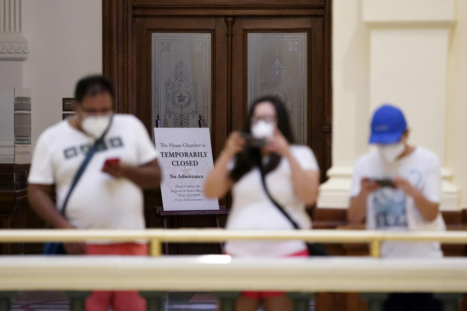 """Visitors take photos near the """"Temporarily Closed"""" doors to the House Chamber at the State Capitol, Tuesday, June 1, 2021, in Austin, Texas. The Texas Legislature closed out its regular session Monday, but are expected to return for a special session after Texas Democrats blocked one of the nation's most restrictive new voting laws with a walkout. (AP Photo/Eric Gay)"""