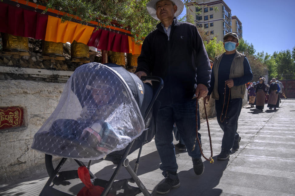A man holds prayer beads and pushes a child in a stroller as he circumambulates around a neighborhood Tibetan Buddhist shrine in the Chengguan district of Lhasa in western China's Tibet Autonomous Region, as seen during a rare government-led tour of the region for foreign journalists, Thursday, June 3, 2021. Long defined by its Buddhist culture, Tibet is facing a push for assimilation and political orthodoxy under China's ruling Communist Party. (AP Photo/Mark Schiefelbein)