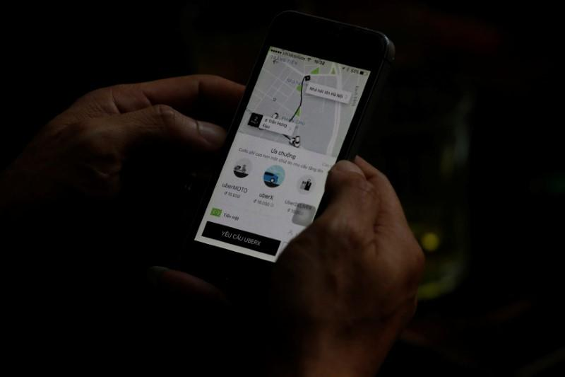 FILE PHOTO: A client uses a smartphone to book Uber service in Hanoi