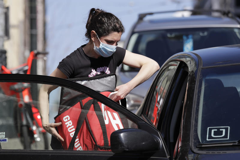 Food delivery driver Dori McGuire Guy wears a protective mask as she loads a take-out order into her car at the Pike Place Market, Friday, March 20, 2020, in Seattle. Restaurants, except for take-out orders, are closed, workers who can are working from home and people are being asked to maintain physical distance from others to help stop the spread of COVID-19. Washington state health officials reported eight new coronavirus deaths on Friday, bringing the total to 83. Seven of those deaths were in King County, the epicenter of the outbreak in the state. (AP Photo/Elaine Thompson)