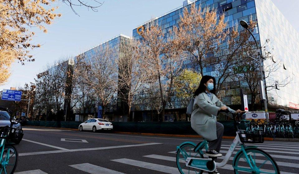 A woman rides past the headquarters of Didi Chuxing in Beijing last year. Photo: Reuters