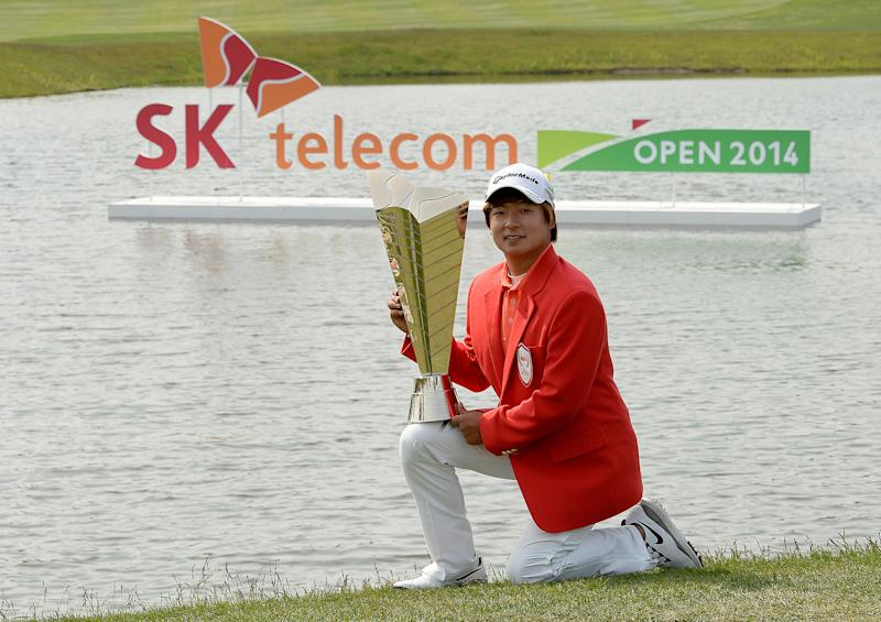South Korea's Kim Seung-hyuk celebrates with the winner's trophy after the final round of the 2014 SK Telecom Open in Seoul on May 18, 2014