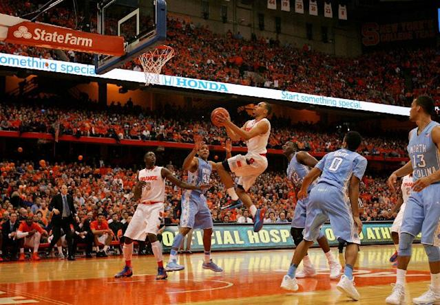 Syracuse's Tyler Ennis, center, drives to the basket in the second half of an NCAA college basketball game against North Carolina in Syracuse, N.Y., Saturday, Jan. 11, 2014. Syracuse won 57-45. (AP Photo/Nick Lisi)