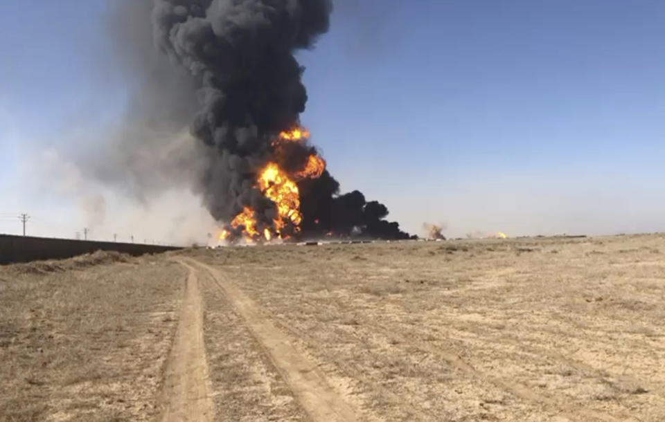 In this still image taken from video, smoke rises from fuel tankers at the Islam Qala border with Iran, in Herat Province, west of Kabul, Afghanistan, Saturday, Feb. 13, 2021. A fuel tanker exploded Saturday at the Islam Qala crossing in Afghanistan's western Herat province on the Iranian border, injuring at least seven people and causing a massive fire that consumed more than 500 trucks carrying natural gas and fuel, according to Afghan officials and Iranian state media. (AP Photo)