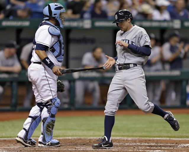 Seattle Mariners' Brad Miller, right, gets a bat from Tampa Bay Rays catcher Jose Molina after scoring on a fourth inning double by teammate Nick Franklin off Tampa Bay Rays starting pitcher David Price during a baseball game Wednesday, Aug. 14, 2013, in St. Petersburg, Fla. (AP Photo/Chris O'Meara)