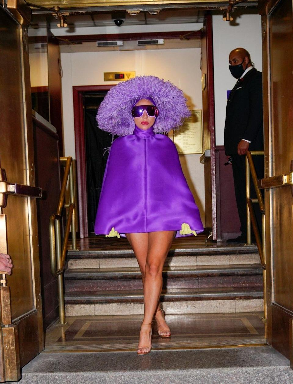 """<p>Ahead of her concert with Tony Bennet, Gaga stepped out in a daring purple ensemble. The singer paired a Valentino Haute Couture Poncho dress with a feather Philip Treacy hat and clear heels.</p><p><a class=""""link rapid-noclick-resp"""" href=""""https://www.net-a-porter.com/en-gb/shop/designer/valentino"""" rel=""""nofollow noopener"""" target=""""_blank"""" data-ylk=""""slk:SHOP VALENTINO NOW"""">SHOP VALENTINO NOW</a></p>"""