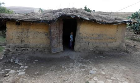 A boy is seen in front of his home built with mud and stone, and roofed with wicker and thatch  in Oued al-Berber