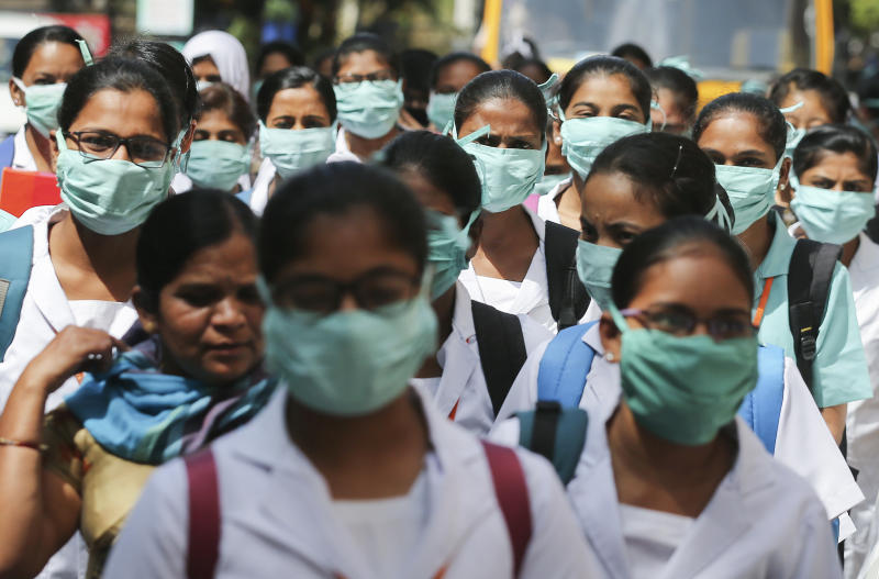 FILE - In this March 6, 2020, file photo, Indian nursing students wearing masks walk in a group at government run Gandhi Hospital in Hyderabad, India. As cases of the coronavirus surge in Italy, Iran, South Korea, the U.S. and elsewhere, many scientists say it's plain that the world is in the grips of a pandemic — a serious global outbreak.  (AP Photo/Mahesh Kumar A.)