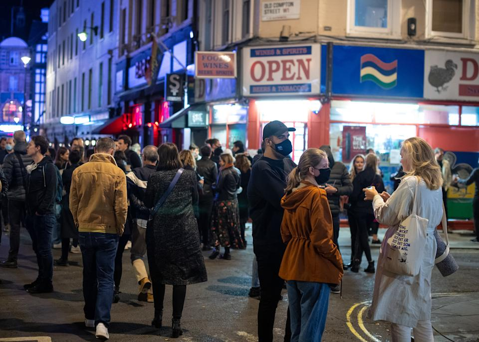 People leave bars and restaturants at closing time in Soho, London, the day after pubs and restaurants were subject to a 10pm curfew to combat the rise in coronavirus cases in England.