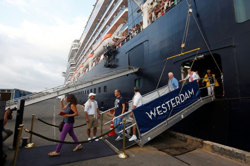 Passengers leave MS Westerdam, a cruise ship that spent two weeks at sea after being turned away by five countries over fears that someone aboard might have the coronavirus, as it docks in Sihanoukville