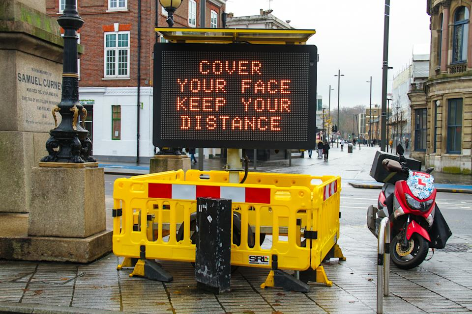 LONDON, UNITED KINGDOM - 2020/12/22: A 'Cover Your Face Keep Your Distance' electronic billboard on the Broadway in Stratford. London and parts of southeast England were put into Tier 4, a tightened measure due to the high presence of the new covid 19 strain. In England, only households living outside a Tier 4 area will be allowed to mix for Christmas and only on Christmas Day. The tier 4 measures are to be reviewed after 30th December. (Photo by David Mbiyu/SOPA Images/LightRocket via Getty Images)