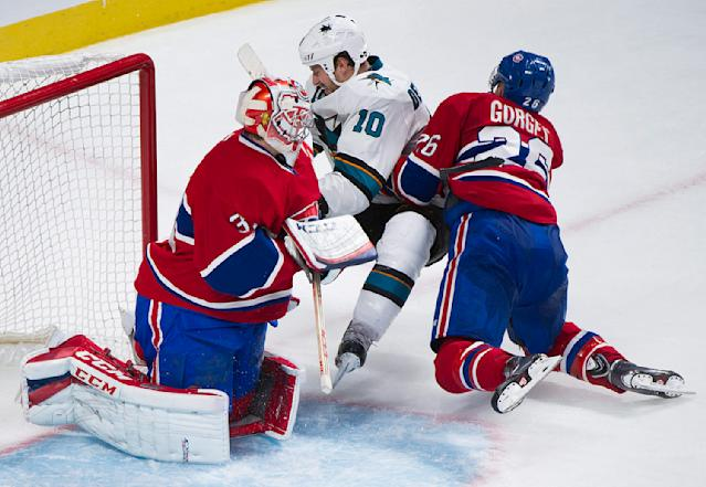 San Jose Sharks' Andrew Desjardins, center, collides with Montreal Canadiens goaltender Carey Price, left, and Canadiens' Josh Gorges during the second period of an NHL hockey game in Montreal, Saturday, Oct. 26, 2013. (AP Photo/The Canadian Press, Graham Hughes)