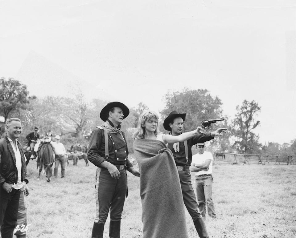 <p>John Wayne and William Holden show Constance Towers how to shoot a revolver on the set of the classic Western movie.</p>