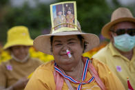 A supporter of the monarchy with an inhaler stuck in her nose, displays an image of King Maha Vajiralongkorn and Queen Suthida as she joins a gathering in front of the Grand Place in Bangkok, Thailand, Sunday, Nov. 1, 2020. Hundreds of royalists gathered close to the Grand Palace in which King Maha Vajiralongkorn is scheduled to visit for a Buddhist religious ceremony. (AP Photo/Wason Wanichakorn)