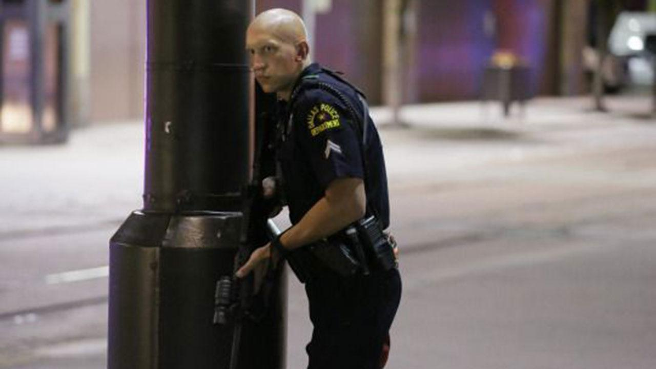 A Dallas policeman keeps watch on a street in downtown Dallas, Thursday, July 7, 2016, following reports that shots were fired during a protest over two recent fatal police shootings of black men. (AP Photo/LM Otero)